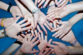 unos chicos juntan sus manos para representar unidad