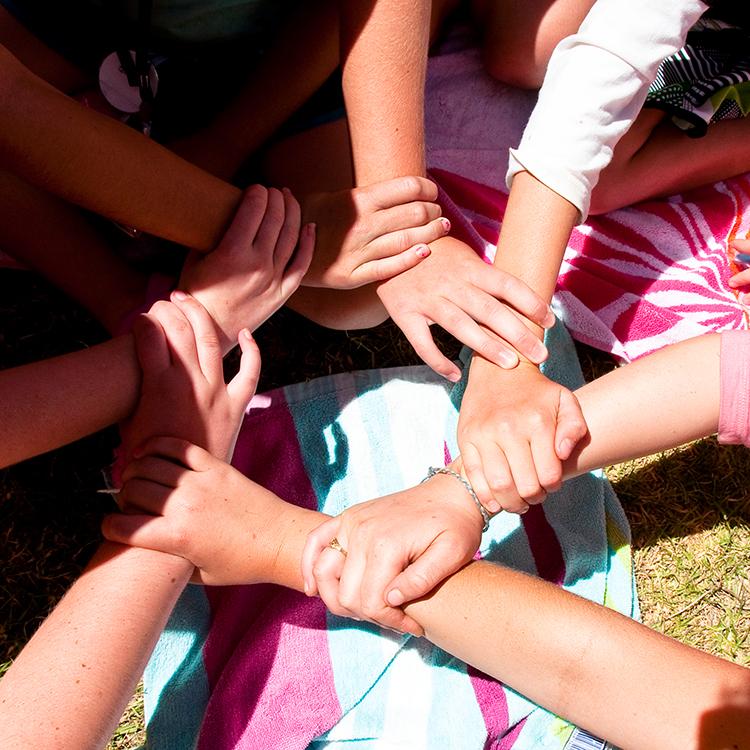 varios chicos juntan sus manos en razon al trabajo en equipo