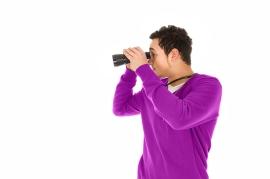 un hombre observa a su izquierda con ayuda de binoculares